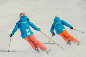 Two instructors carving with speed, skiing need for speed