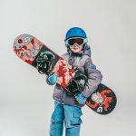 Oxygène Ski & Snowboard School Child Holding Snowboard