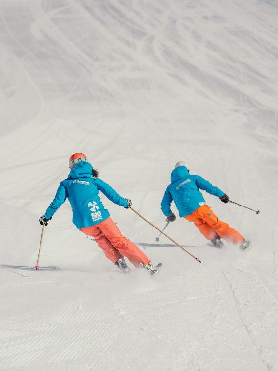 Oxygène Ski & Snowboard School – Instructors Skiing with Oxygène Logo