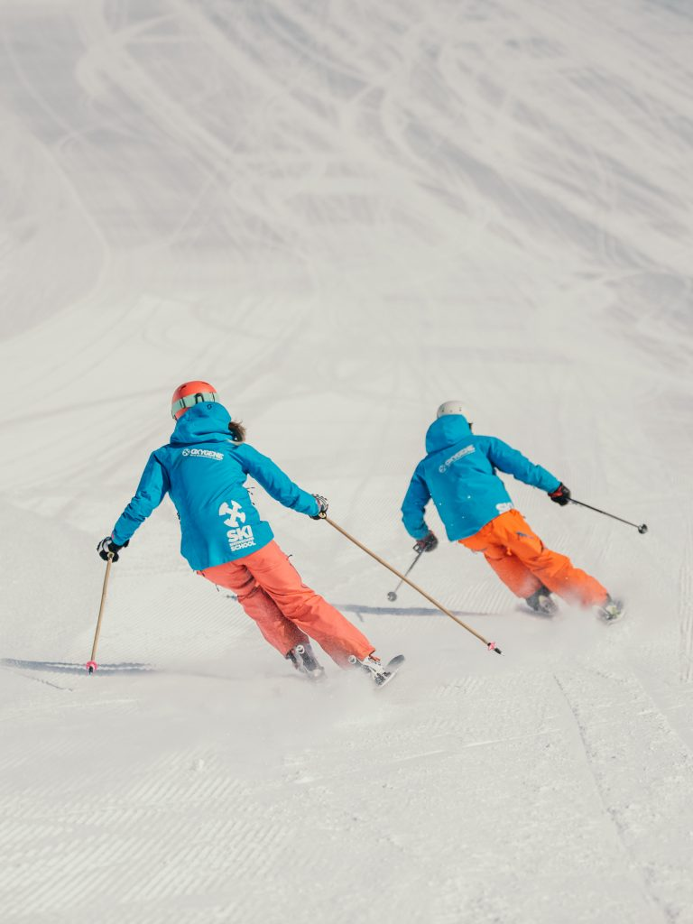 Oxygène Ski & Snowboard School – Instructors Skiing with Oxygène Logo