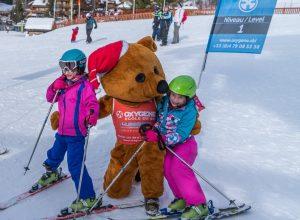 ollie oxygene bear hugging children skiing